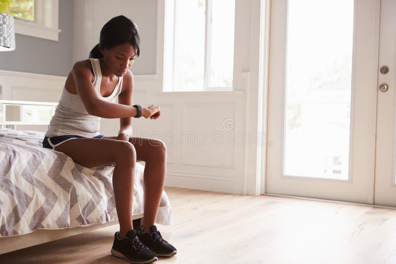 Νέα μαύρη γυναίκα έτοιμη για την άσκηση, που ελέγχει το έξυπνο ρολόι στοκ φωτογραφία
