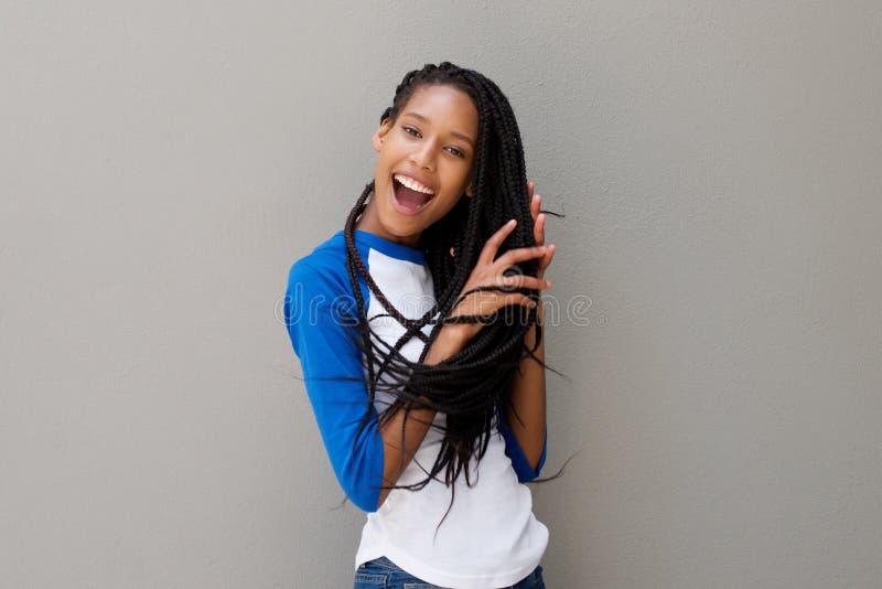 Νέα μαύρη γυναίκα με την πλεγμένη τρίχα που γελά ενάντια στον γκρίζο τοίχο στοκ εικόνες