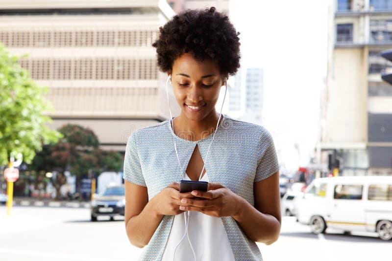 Νέα μαύρη γυναίκα που ακούει τη μουσική στο τηλέφωνο κυττάρων της στοκ φωτογραφία
