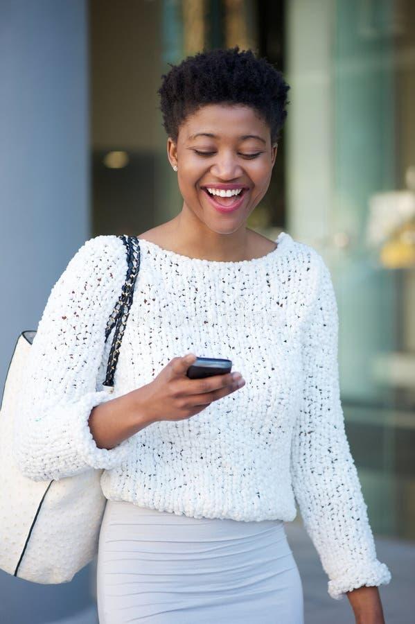 Νέα μαύρη γυναίκα που γελά και που διαβάζει το μήνυμα κειμένου στοκ εικόνα