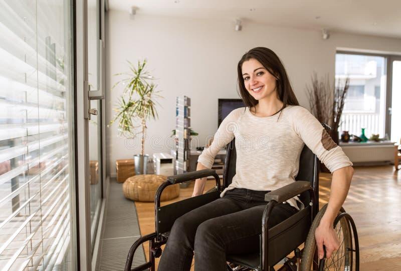 Νέα με ειδικές ανάγκες γυναίκα στην αναπηρική καρέκλα στο σπίτι στο καθιστικό στοκ εικόνες