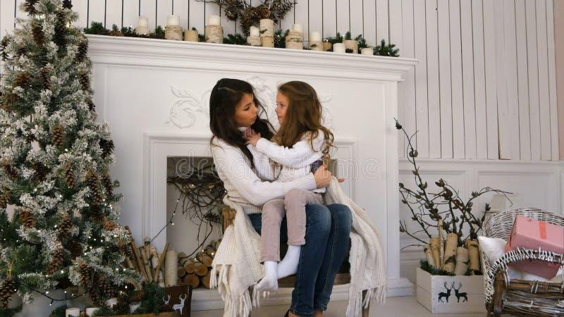 Νέα μητέρα και η κόρη της που καθίστανται άνετος σε μια καρέκλα κοντά στην εστία στοκ φωτογραφίες με δικαίωμα ελεύθερης χρήσης