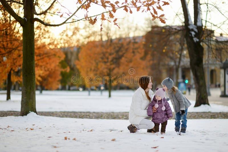 Νέα μητέρα και τα παιδιά της που έχουν τη διασκέδαση το χειμώνα στοκ εικόνα