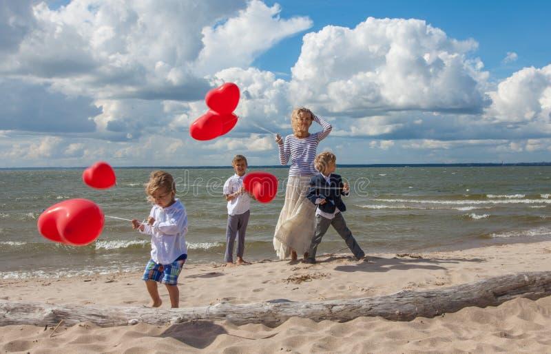 Νέα μητέρα και τρία παιδιά με τα κόκκινα μπαλόνια στοκ φωτογραφία