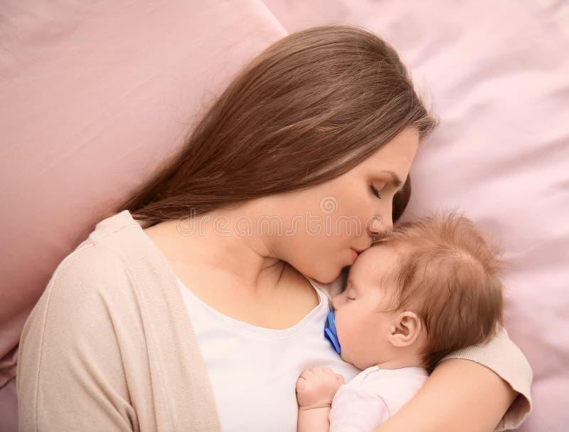 Νέα μητέρα και χαριτωμένος ύπνος μωρών στο κρεβάτι στοκ φωτογραφία
