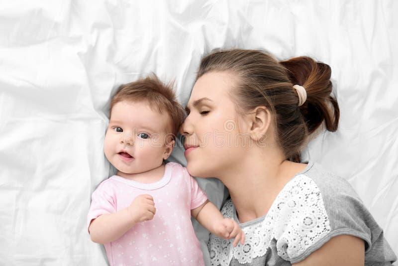 Νέα μητέρα και χαριτωμένο μωρό στο κρεβάτι στοκ φωτογραφίες