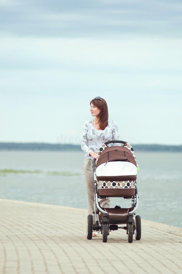 Νέα μητέρα με έναν περιπατητή στοκ φωτογραφίες