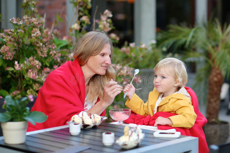 Νέα μητέρα με λίγη κόρη που τρώει το παγωτό υπαίθρια στον καφέ στοκ φωτογραφίες