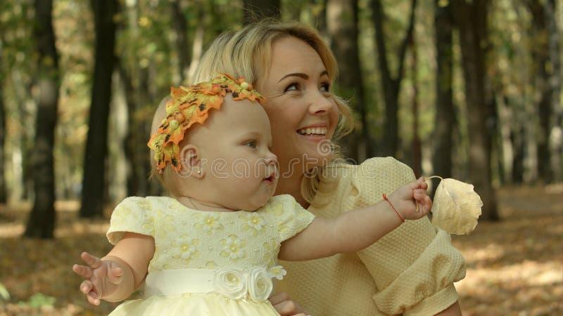 Νέα μητέρα με την κόρη μωρών της στο πάρκο φθινοπώρου στοκ φωτογραφία με δικαίωμα ελεύθερης χρήσης