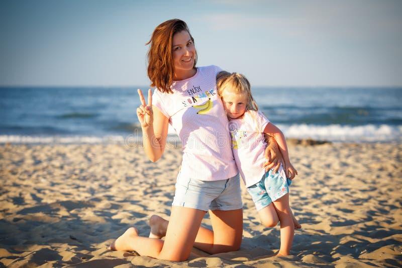 Νέα μητέρα με την κόρη στην παραλία στοκ εικόνες