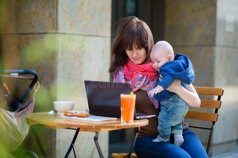 Νέα μητέρα με το αγοράκι της που εργάζεται στον καφέ στοκ φωτογραφία με δικαίωμα ελεύθερης χρήσης