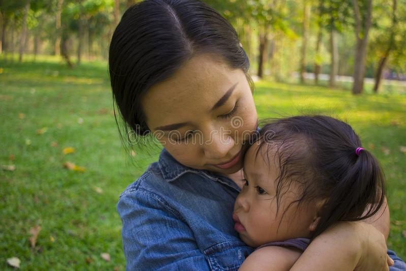 Νέα μητέρα που αγκαλιάζει και κατευναστική να φωνάξει λίγη κόρη, ασιατική μητέρα που προσπαθεί να ανακουφίσει και να ηρεμήσει κάτ στοκ εικόνες