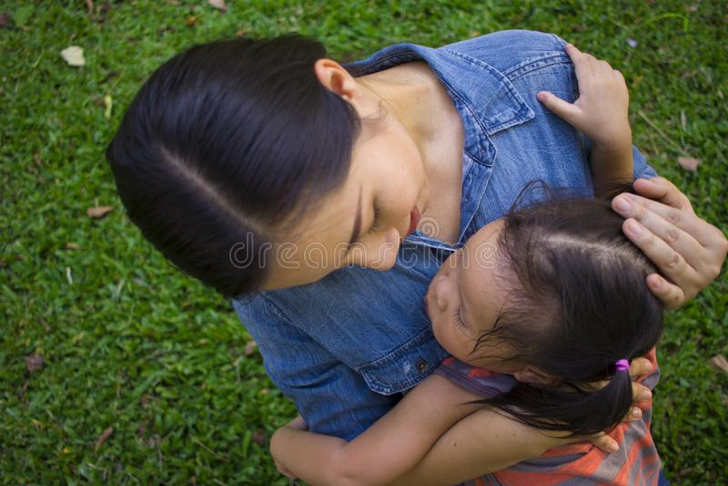 Νέα μητέρα που αγκαλιάζει και κατευναστική να φωνάξει λίγη κόρη, ασιατική μητέρα που προσπαθεί να ανακουφίσει και να ηρεμήσει κάτ στοκ εικόνα