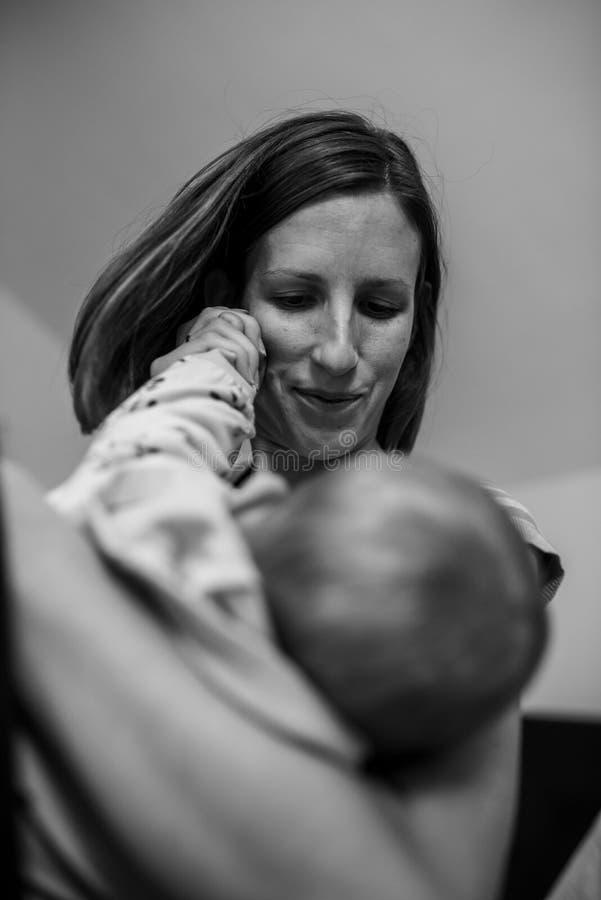 Νέα μητέρα που αγκαλιάζει στοργικά το μωρό της στοκ φωτογραφία
