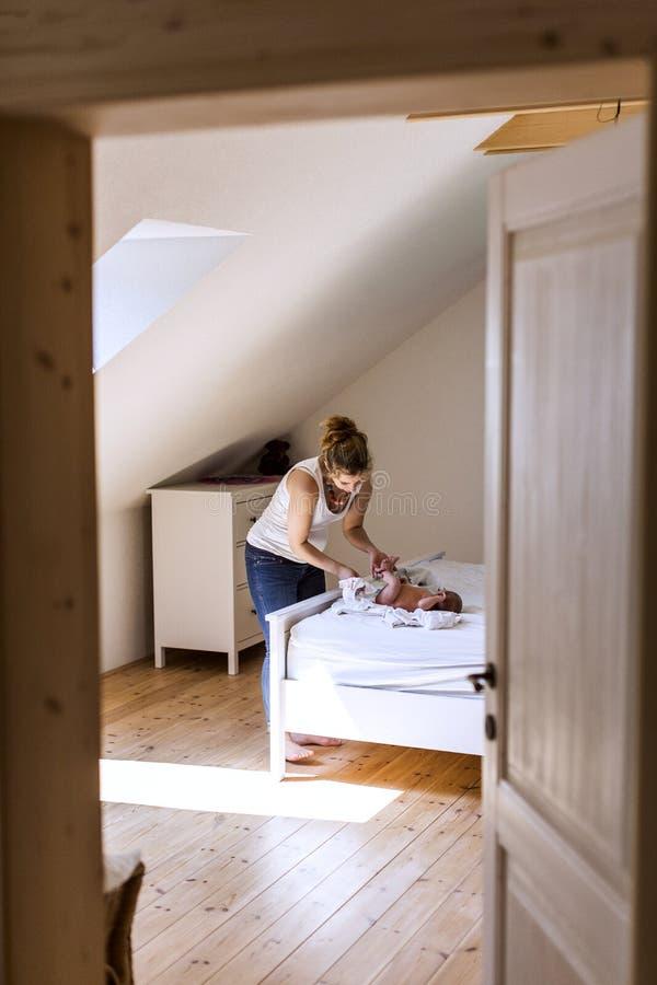 Νέα μητέρα που αλλάζει στο σπίτι την πάνα στο κοριτσάκι της στοκ εικόνα