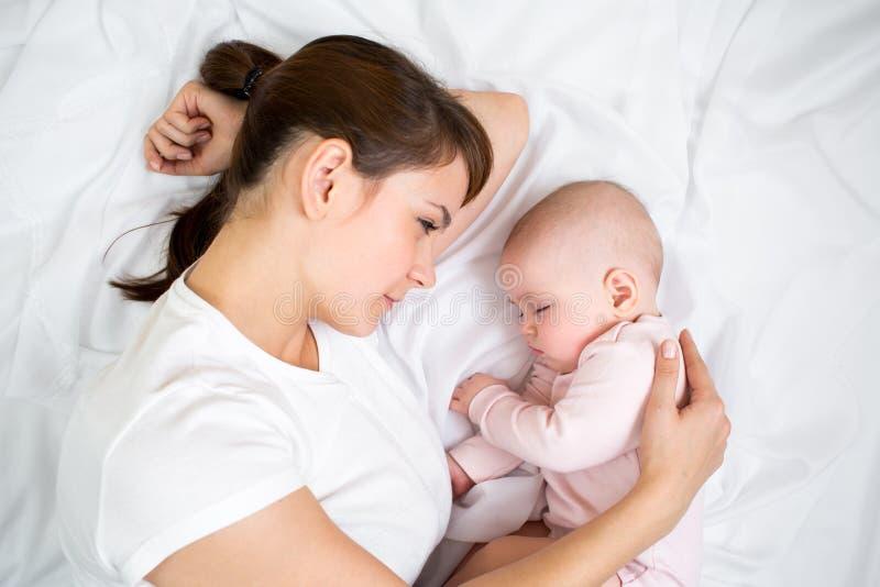 Νέα μητέρα που εξετάζει το κοριτσάκι ύπνου της στοκ φωτογραφίες με δικαίωμα ελεύθερης χρήσης