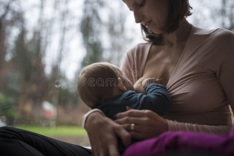 Νέα μητέρα που θηλάζει το μικροσκοπικό μωρό της στοκ φωτογραφία με δικαίωμα ελεύθερης χρήσης