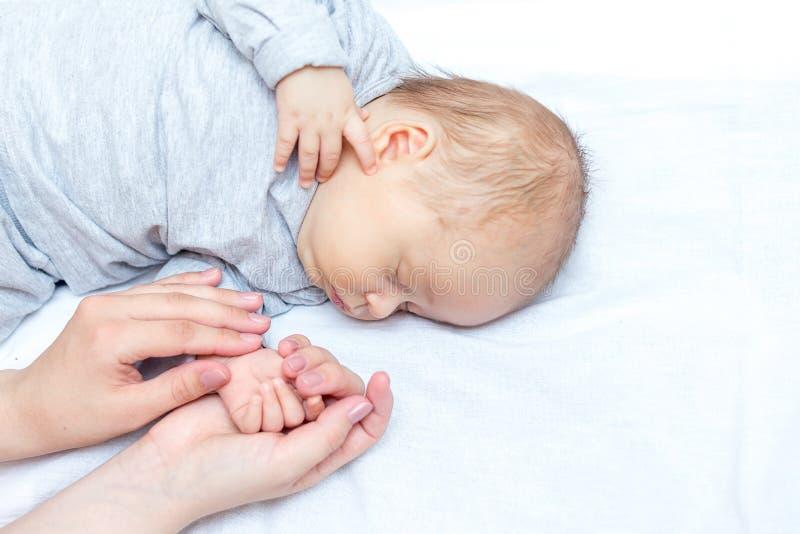 Νέα μητέρα που κρατά το νεογέννητο χέρι παιδιών της στοκ φωτογραφίες