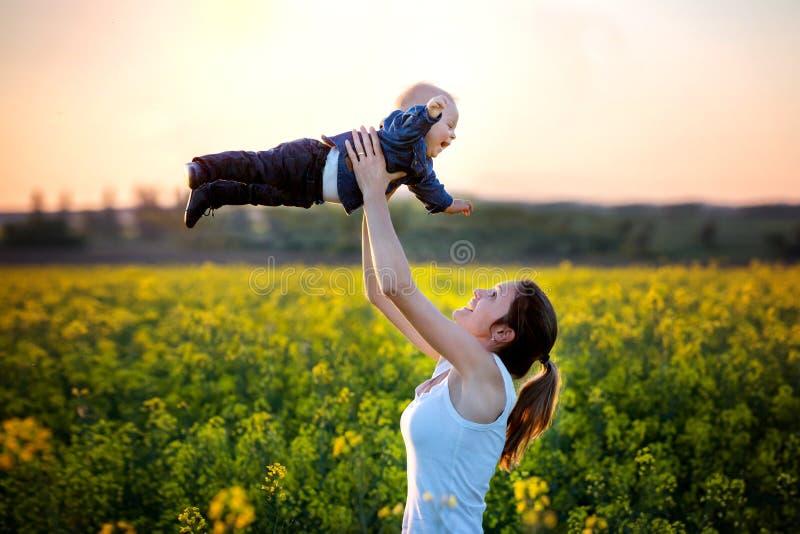 Νέα μητέρα που κρατά ψηλά το γιο todller της στον τομέα canola στοκ εικόνα με δικαίωμα ελεύθερης χρήσης