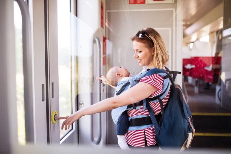 Νέα μητέρα που ταξιδεύει με το μωρό με το τραίνο στοκ εικόνα με δικαίωμα ελεύθερης χρήσης