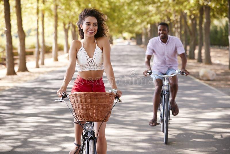 Νέα μικτά οδηγώντας ποδήλατα ζευγών φυλών σε έναν δενδρώδη δρόμο στοκ εικόνα