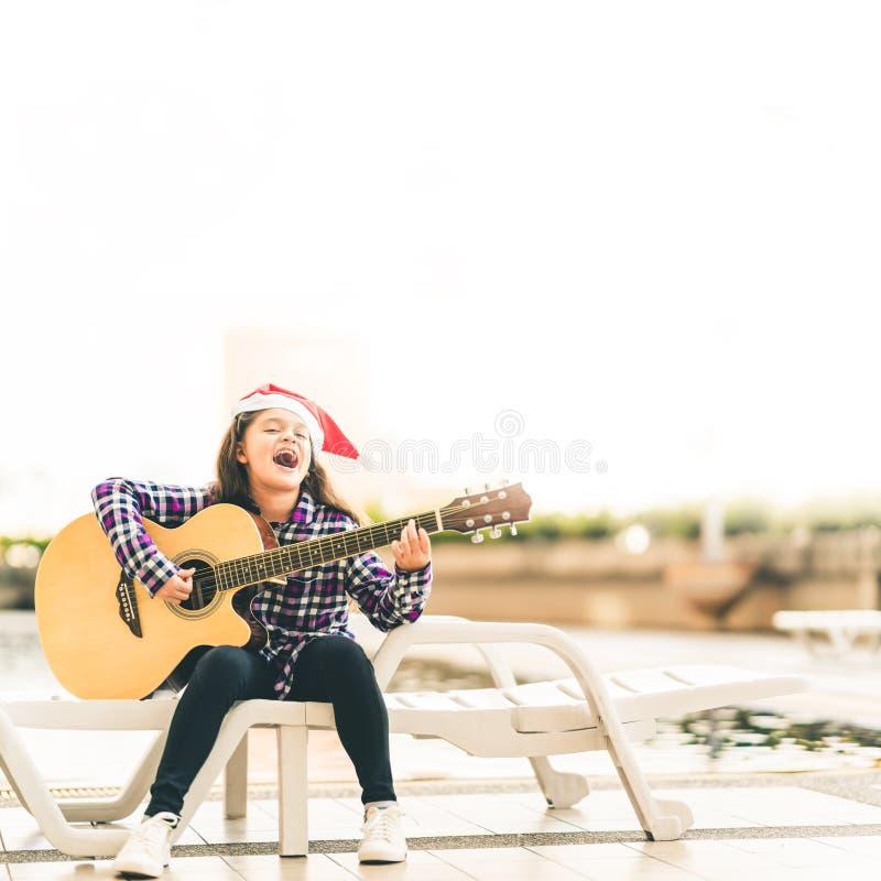 Νέα μικτή κιθάρα παιχνιδιού κοριτσιών αγώνων, τραγούδι και χαμόγελο χαρωπά από την πισίνα, με το καπέλο santa Χριστουγέννων, έννο στοκ εικόνες με δικαίωμα ελεύθερης χρήσης