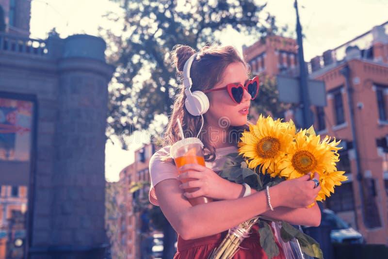 Νέα μοντέρνη γυναίκα που εξετάζει τους φωτεινούς κίτρινους ηλίανθους περπατώντας στοκ εικόνες