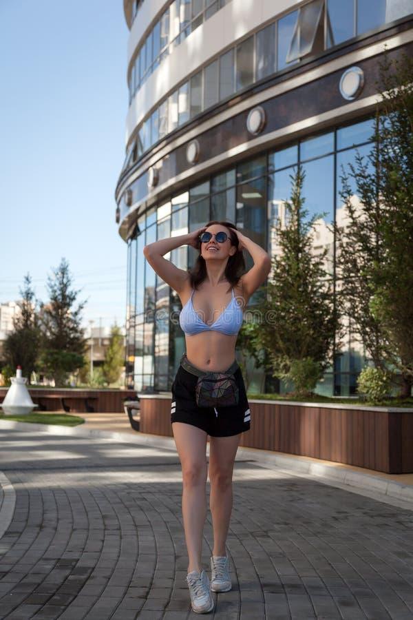 Νέα μοντέρνη γυναίκα που περπατά σε μια οδό πόλεων στοκ φωτογραφίες