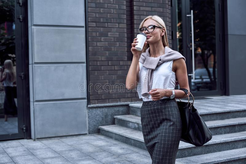 Νέα μοντέρνη γυναίκα που περπατά στην οδό κεντρικός με το χαμόγελο στοκ φωτογραφίες