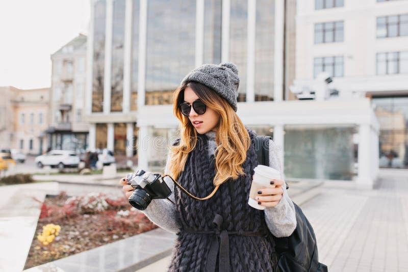 Νέα μοντέρνη γυναίκα στο θερμό μάλλινο πουλόβερ, τα σύγχρονα γυαλιά ηλίου και το πλεκτό καπέλο που περπατά με τον καφέ για να πάε στοκ εικόνα με δικαίωμα ελεύθερης χρήσης