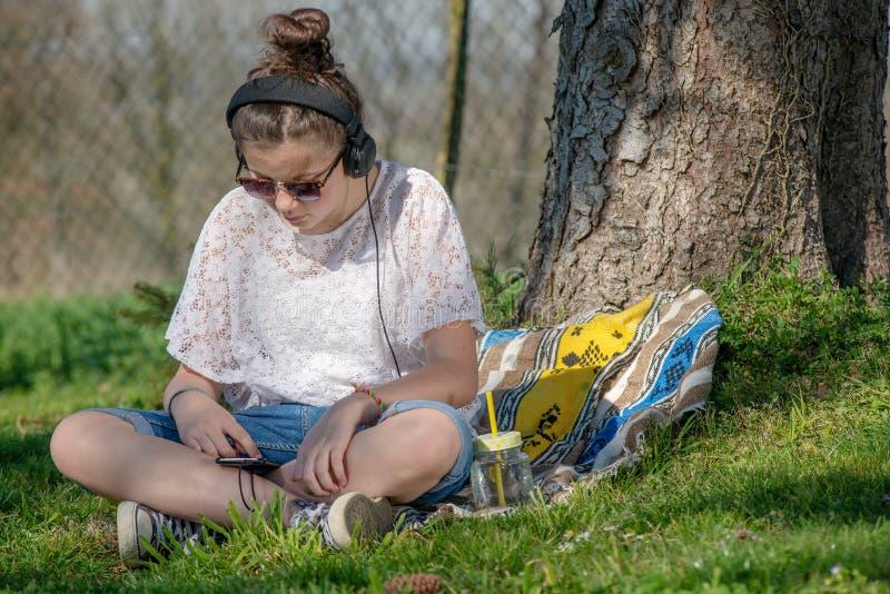 Νέα μουσική ακούσματος κοριτσιών εφήβων με το ακουστικό στο πάρκο στοκ εικόνες