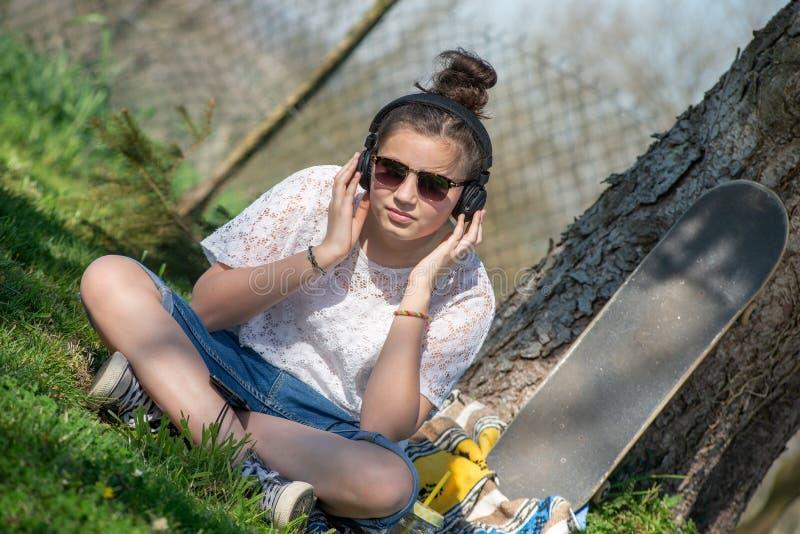 Νέα μουσική ακούσματος κοριτσιών εφήβων με το ακουστικό στο πάρκο στοκ εικόνα