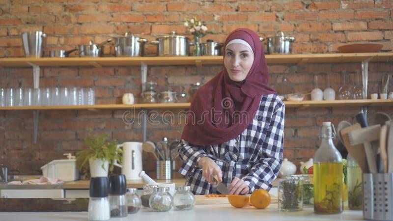 Νέα μουσουλμανική γυναίκα στα λαχανικά περικοπών κουζινών για να μαγειρεψει τα τρόφιμα στοκ εικόνες με δικαίωμα ελεύθερης χρήσης