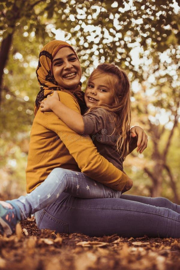 Νέα μουσουλμανική μητέρα στο αγκάλιασμα με την κόρη στοκ φωτογραφία