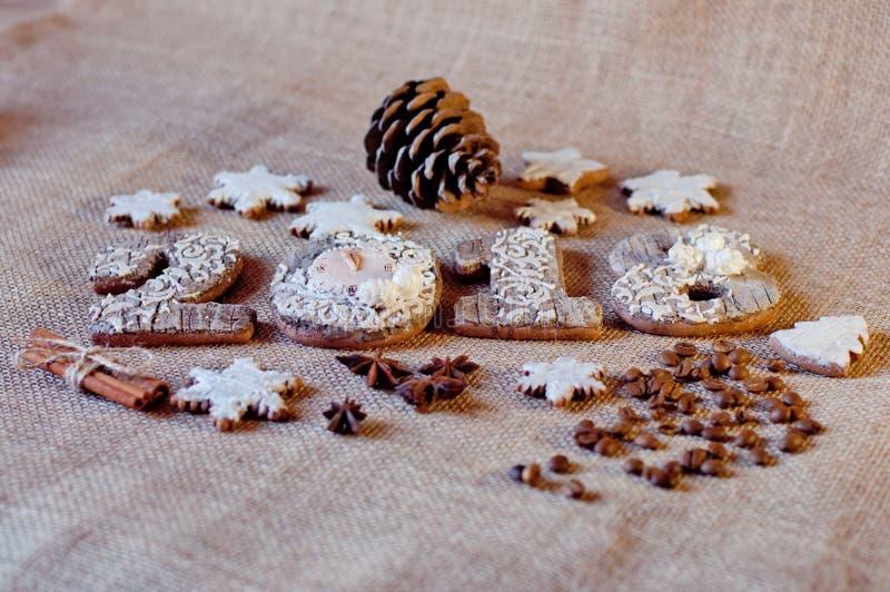 Νέα μπισκότα μελιού διακοπών έτους στη μορφή των αριθμών, αστέρια που βάζουν στο καφετί sackcloth υπόβαθρο στοκ φωτογραφία με δικαίωμα ελεύθερης χρήσης