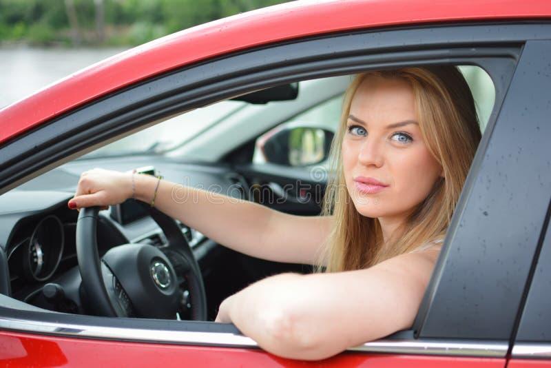Νέα μπλε-eyed ξανθά βλέμματα μέσω του παραθύρου αυτοκινήτων στοκ φωτογραφία με δικαίωμα ελεύθερης χρήσης