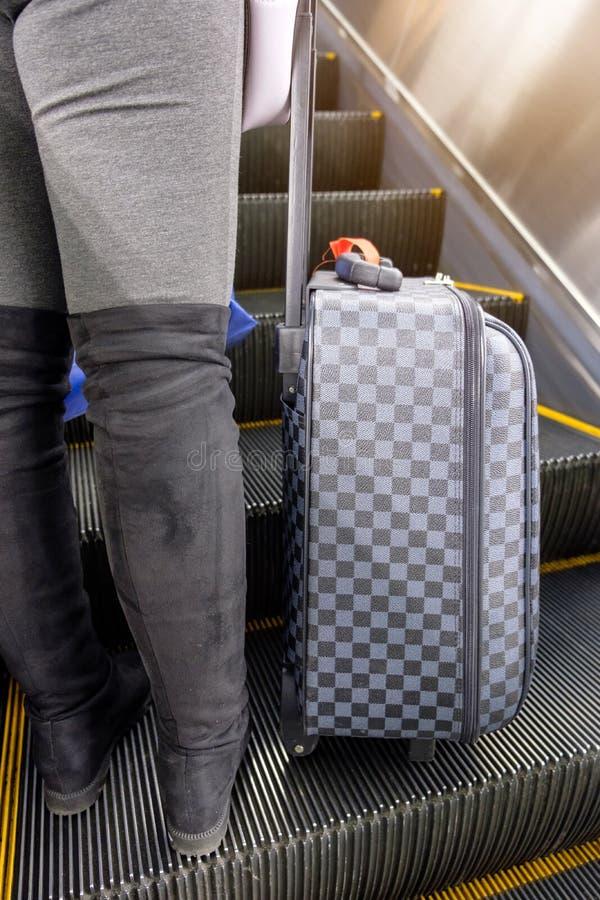 Νέα μπότα ένδυσης γυναικών χαμηλότερη - μισός με τις αποσκευές σκακιού που στέκονται επάνω στοκ εικόνες με δικαίωμα ελεύθερης χρήσης