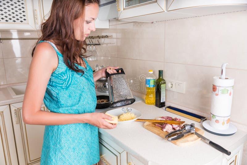 Νέα νοικοκυρά που μαγειρεύει το γεύμα βραδιού στοκ εικόνα με δικαίωμα ελεύθερης χρήσης