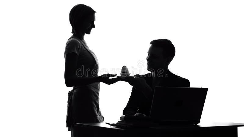 Νέα νοικοκυρά που φέρνει το νόστιμο κέικ για το σύζυγο που εργάζεται στο lap-top, οικογενειακή αγάπη στοκ φωτογραφία