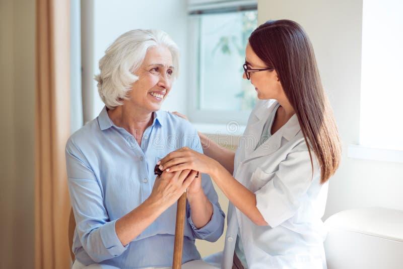 Νέα νοσοκόμα που αγκαλιάζει την ανώτερη γυναίκα στοκ φωτογραφία