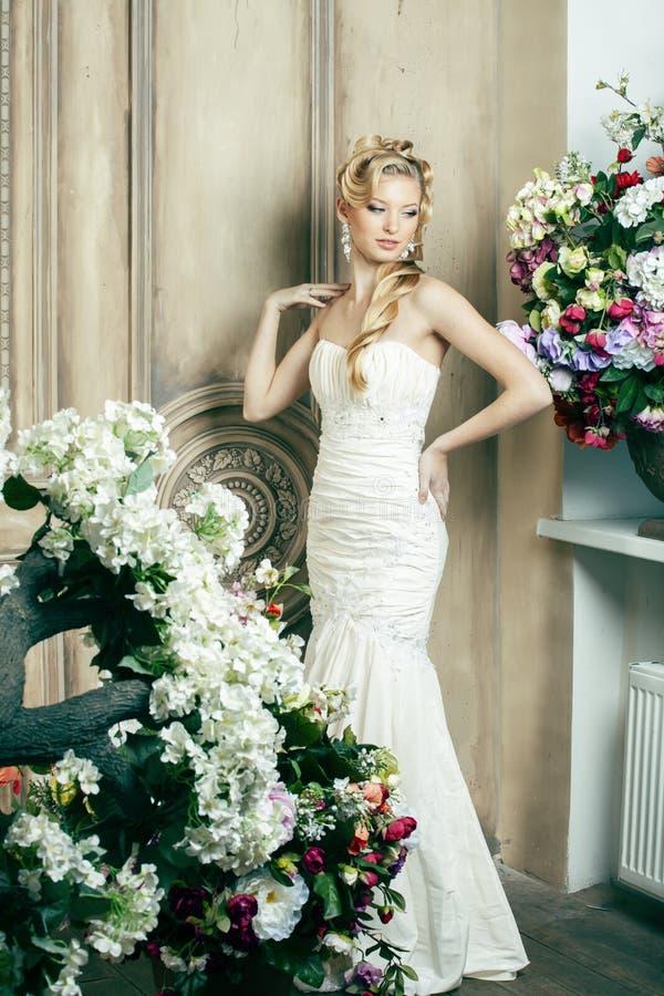 Νέα νύφη ομορφιάς μόνο στο εκλεκτής ποιότητας εσωτερικό πολυτέλειας με πολλά λουλούδια, makeup και δημιουργικό hairstyle στοκ φωτογραφίες