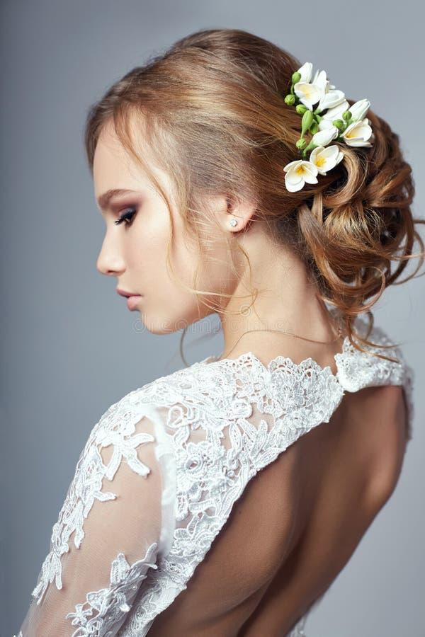 Νέα νύφη σε ένα πολυτελές άσπρο γαμήλιο φόρεμα και ένα όμορφο hai στοκ εικόνες