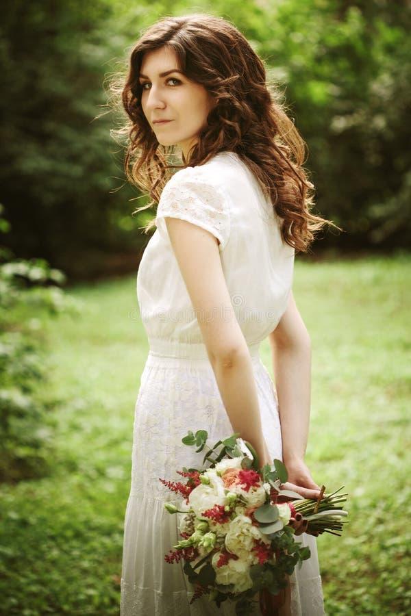 Νέα νύφη στα γαμήλια λουλούδια εκμετάλλευσης πάρκων στοκ εικόνα