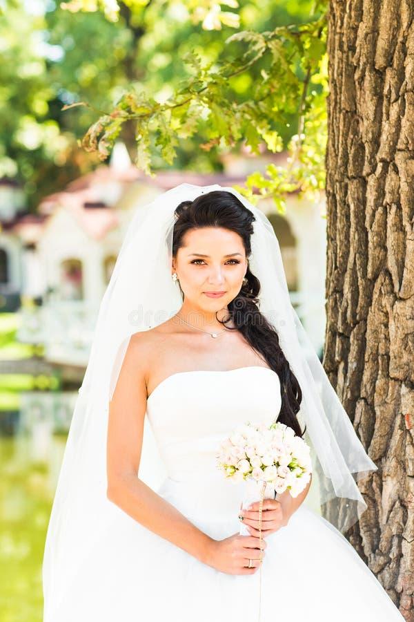 Νέα νύφη στην ανθοδέσμη εκμετάλλευσης γαμήλιων φορεμάτων στοκ εικόνα με δικαίωμα ελεύθερης χρήσης