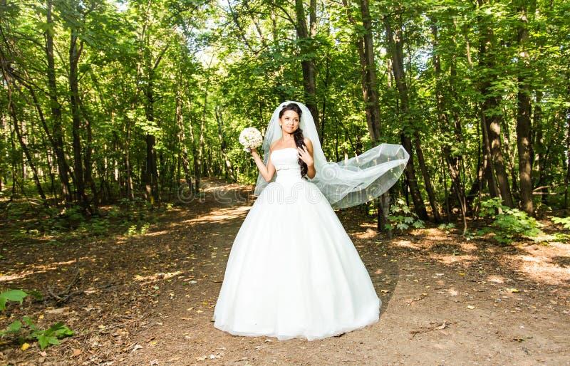 Νέα νύφη στην ανθοδέσμη εκμετάλλευσης γαμήλιων φορεμάτων στοκ εικόνες