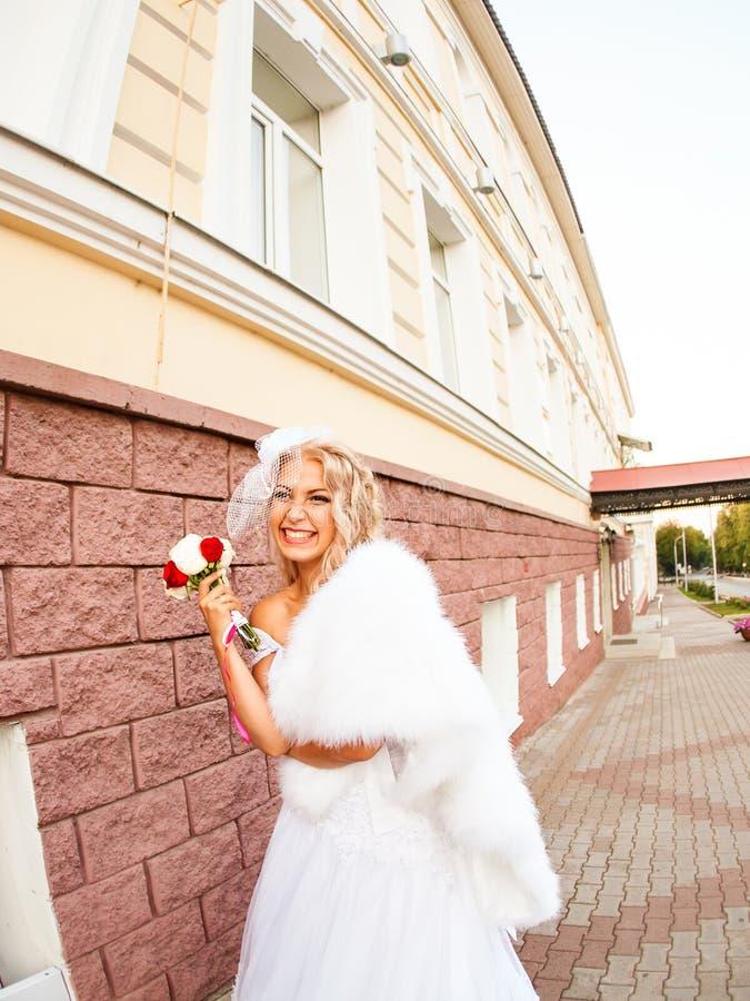 Νέα νύφη στην ανθοδέσμη εκμετάλλευσης γαμήλιων φορεμάτων στοκ φωτογραφία