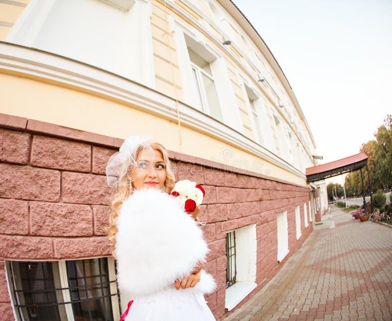 Νέα νύφη στην ανθοδέσμη εκμετάλλευσης γαμήλιων φορεμάτων στοκ φωτογραφίες