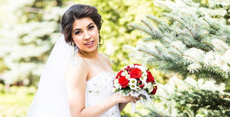 Νέα νύφη στην ανθοδέσμη εκμετάλλευσης γαμήλιων φορεμάτων στοκ εικόνα