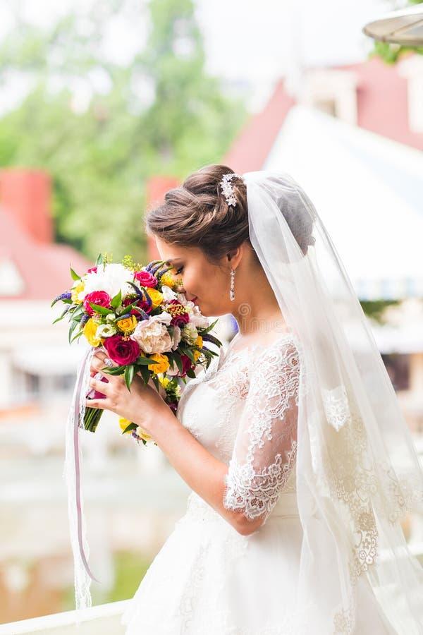 Νέα νύφη στην ανθοδέσμη εκμετάλλευσης γαμήλιων φορεμάτων στοκ φωτογραφία με δικαίωμα ελεύθερης χρήσης