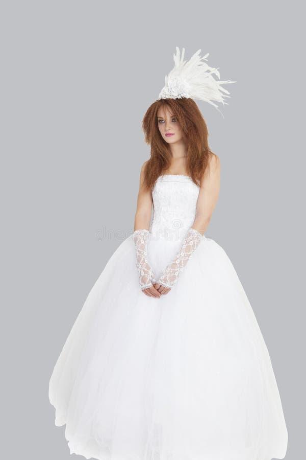 Νέα νύφη brunette που στέκεται στη γαμήλια εσθήτα πέρα από το ανοικτό γκρι υπόβαθρο στοκ φωτογραφία με δικαίωμα ελεύθερης χρήσης